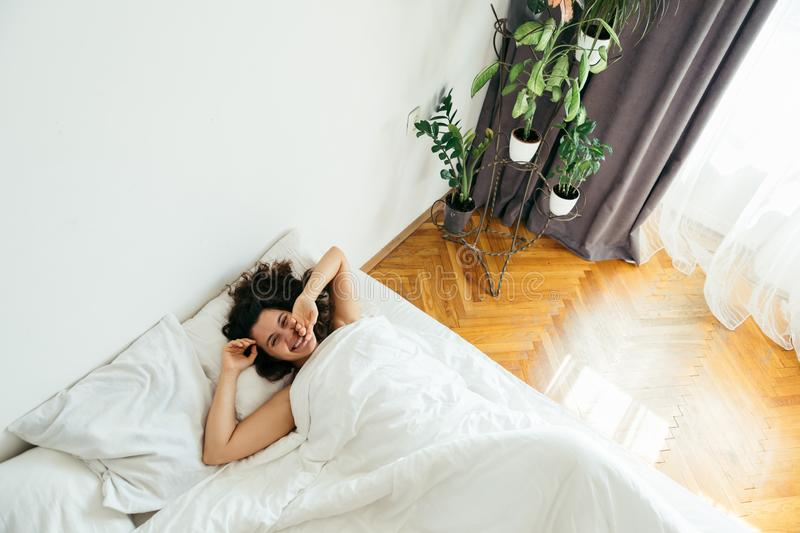 Young pretty woman in bed with white sheets bright light stock photography