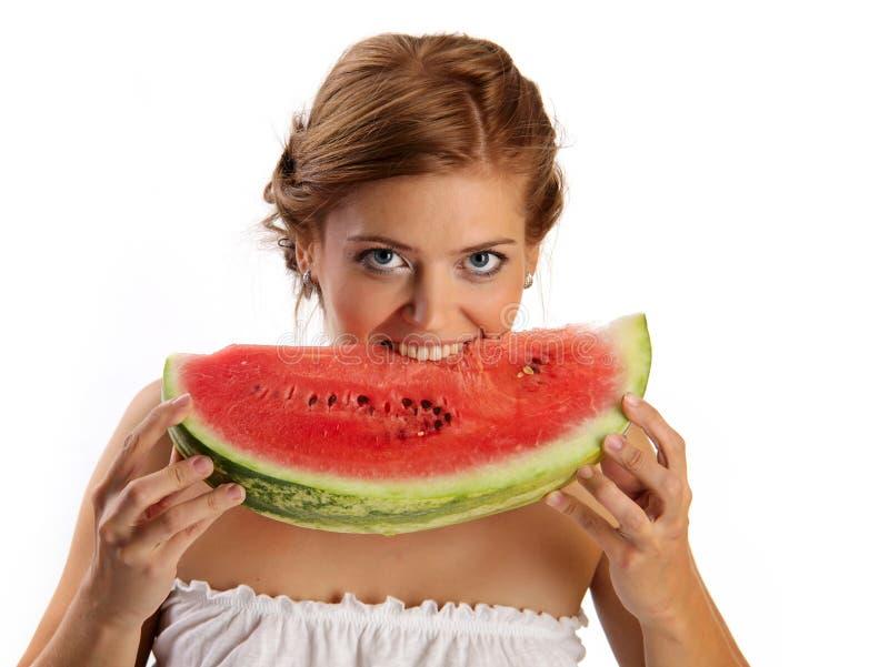 Young pretty woman biting slice of watermelon stock photo