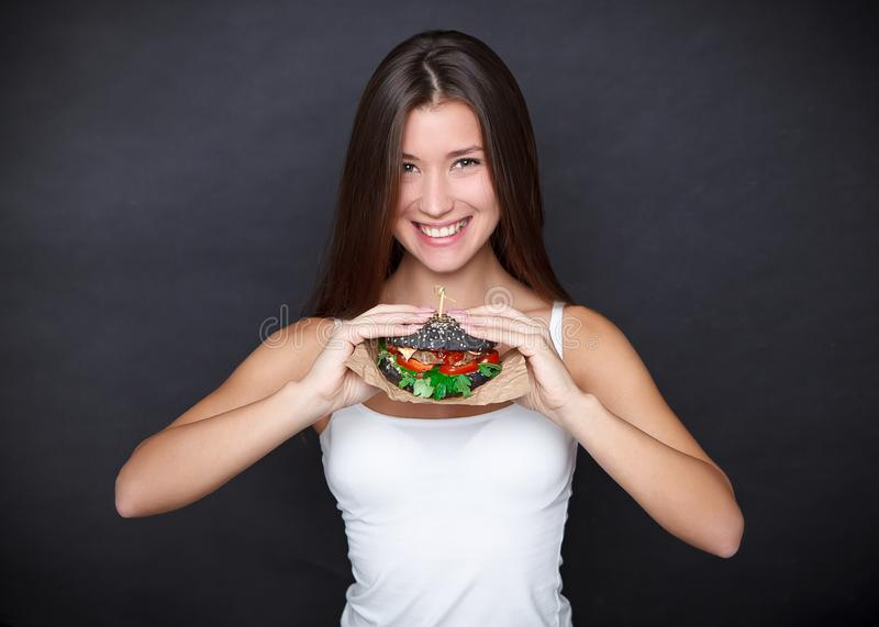 Young pretty woman with black burger in her hands on the dark grey background. Studio. Concept unhealthy, fast food royalty free stock photos