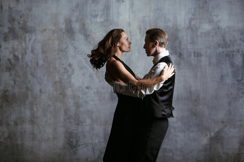 Young pretty woman in black dress and man dance tango stock photos