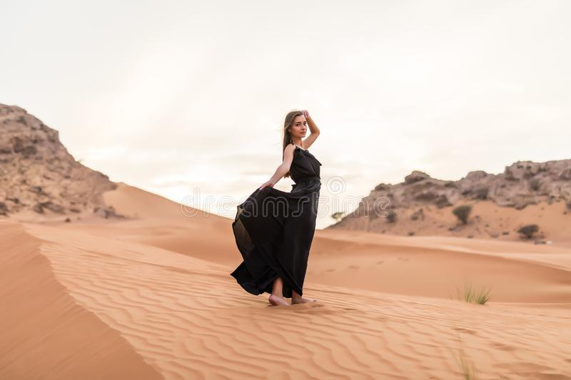 Young pretty woman in black dress stands on dune in desert at sunny hot day royalty free stock photo