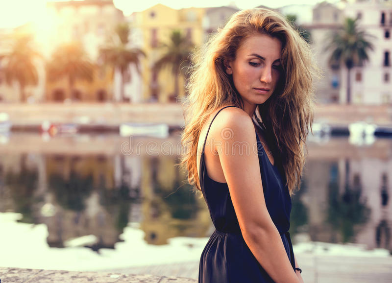 Young pretty woman in black dress, at sunset. Sardinia. Italy. stock image