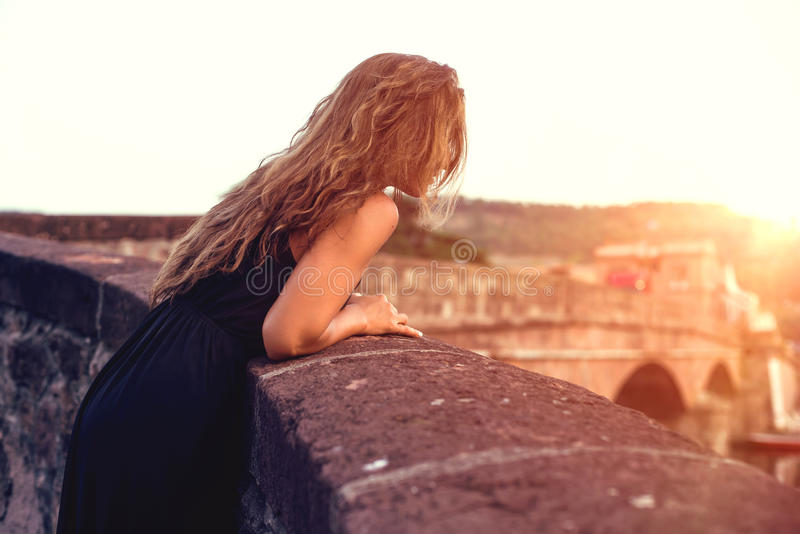 Young pretty woman in black dress, at sunset. Sardinia. Italy. stock photos
