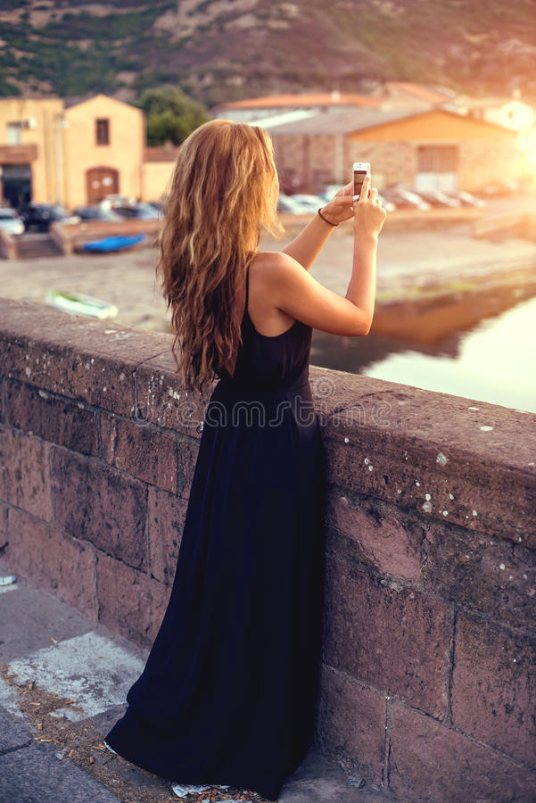 Young pretty woman in black dress taking pictures on the smartphone. Sardinia. Italy. royalty free stock photos