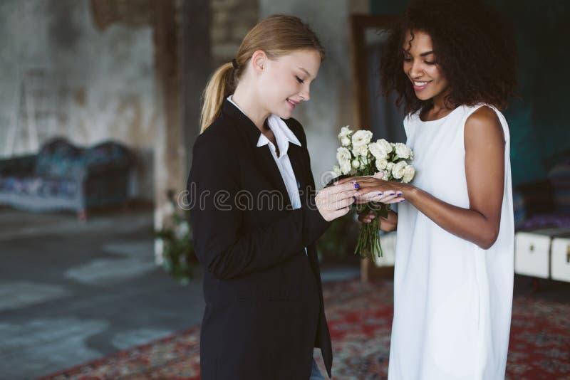 https://thumbs.dreamstime.com/b/young-pretty-woman-blond-hair-black-suit-putting-wedding-ring-beautiful-african-american-woman-dark-curly-hair-181873613.jpg