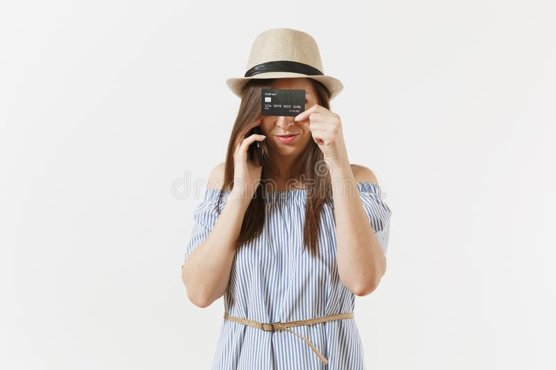 Young pretty woman in blue dress, hat talking on mobile phone, holding, hiding, covering eyes or face by credit card stock image