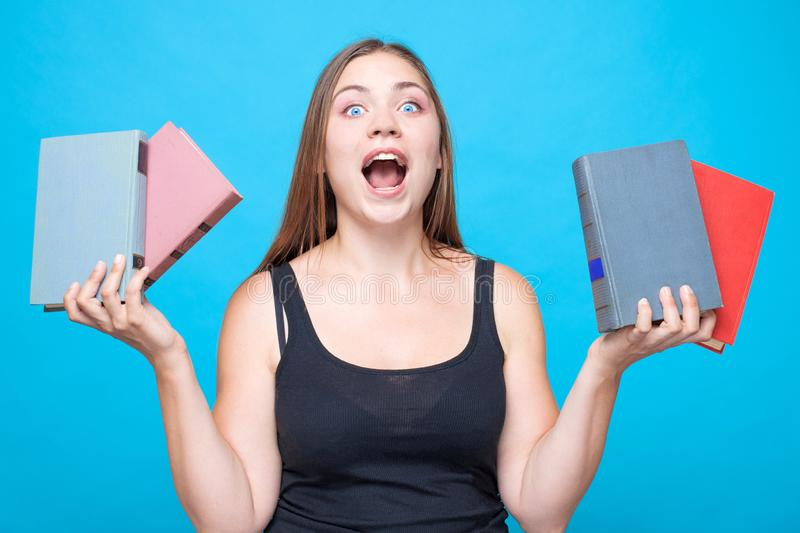 Young pretty woman with 2 books in each hands screams with strong emotions with mouth up. stock image