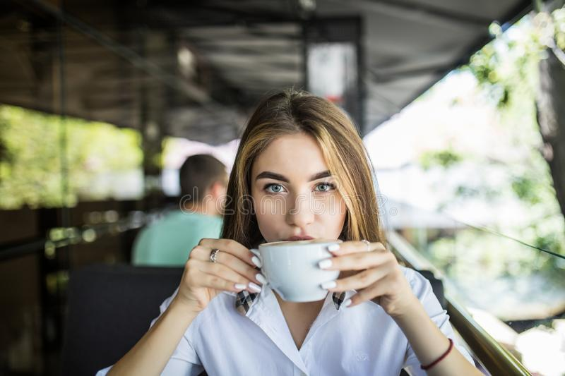 Young pretty woman in a cafe drinking coffee on terrace royalty free stock photography