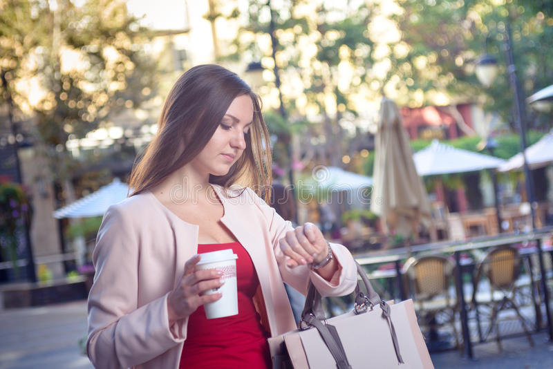 Young pretty woman checking time hurrying down city street stock photos