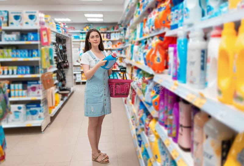 A young pretty woman chooses a cleaning agent in the store. Purchase and sale of goods in the store stock photos