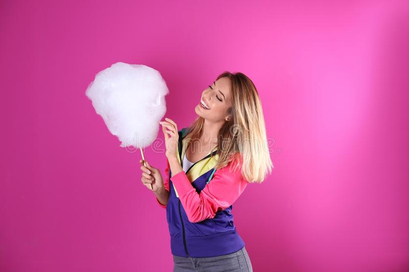 Young pretty woman with cotton candy. On colorful background royalty free stock photography
