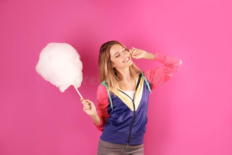 Young pretty woman with cotton candy. On colorful background stock photo