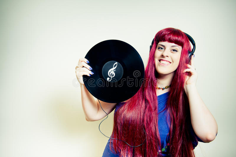 Young pretty woman dancing with headphones and vinyl record royalty free stock photos