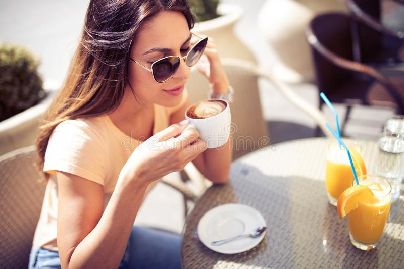 Young pretty woman drinking cappuccino, coffee in cafe outdoors stock photo