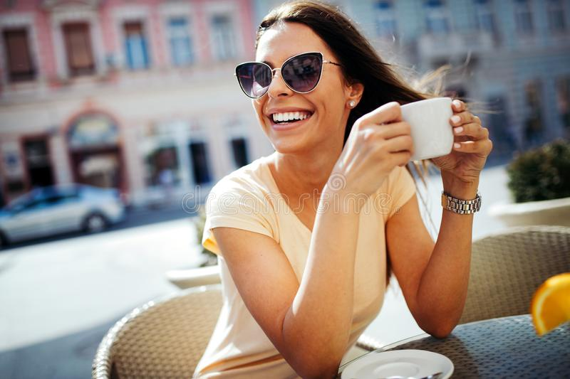 Young pretty woman drinking cappuccino, coffee in cafe outdoors royalty free stock photos