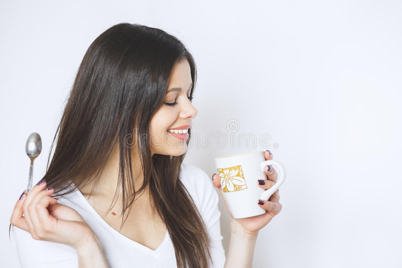 Young pretty woman drinking coffee or tea . Relaxing girl . Woman drinking coffee in the morning at home lifestyle. Studio royalty free stock image
