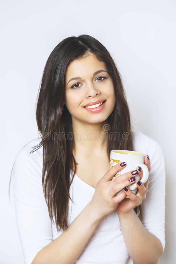 Young pretty woman drinking coffee or tea . Relaxing girl . Woman drinking coffee in the morning at home lifestyle. Studio royalty free stock photo