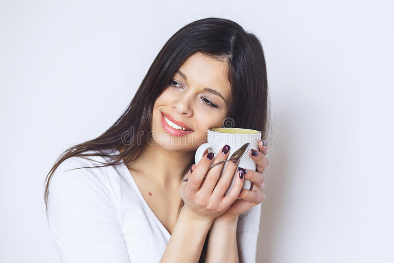 Young pretty woman drinking coffee or tea . Relaxing girl . Woman drinking coffee in the morning at home lifestyle. Studio royalty free stock photography