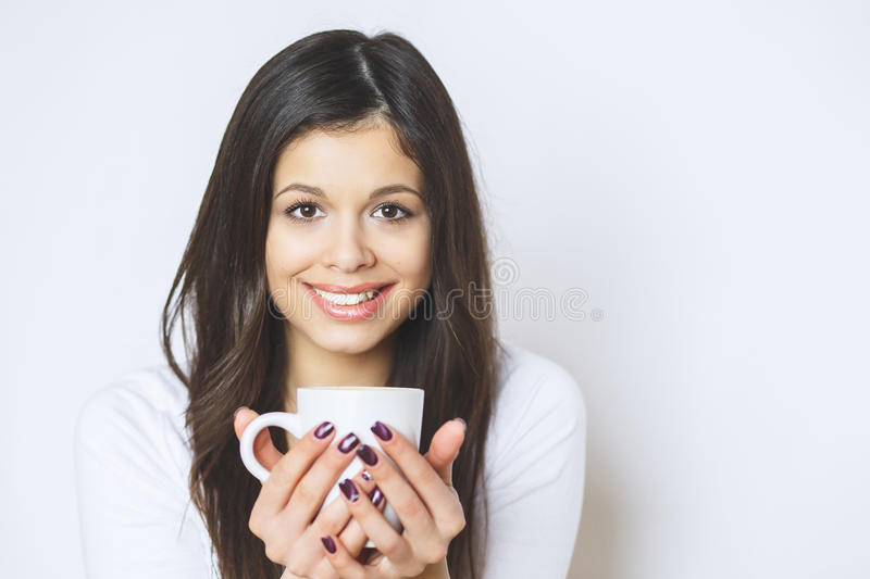 Young pretty woman drinking coffee or tea . Relaxing girl . Woman drinking coffee in the morning at home lifestyle. Studio stock photo