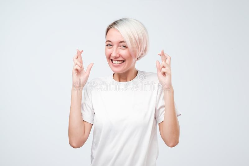 Young pretty woman with dyed hair making a wish crossed her fingers, luck, closed eyes, hopeful gesture stock photography