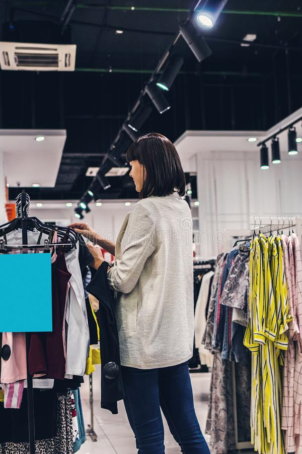 Young pretty woman in the fashion store. Shopping concept. royalty free stock image