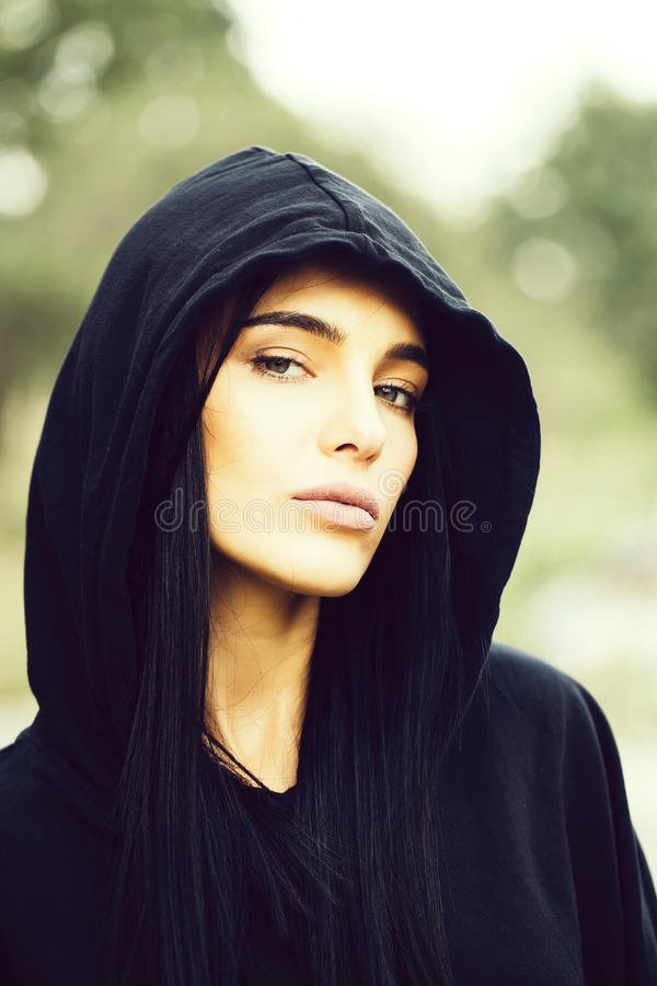 Pretty brunette girl in hood. Young pretty woman or fashionable girl with cute face and brunette hair in black jacket with hood outdoor on blurred or defocused stock photo