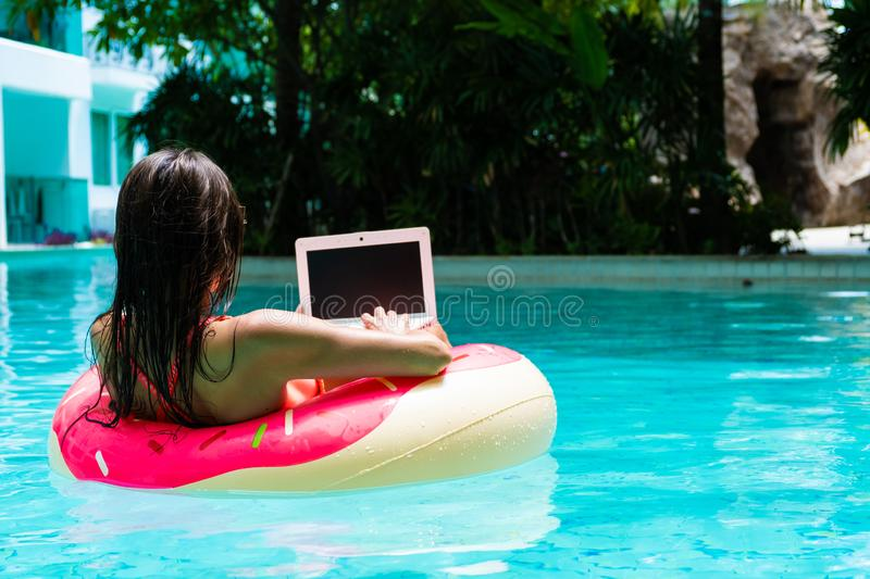 Young pretty woman freelancer is floating on the sea or in the pool in a swimming circle. A girl is relaxing on the royalty free stock photography