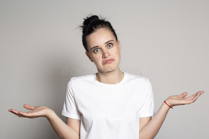 Young, pretty woman with a funny facial expression is surprised and puzzled and raises her hands in confusion. Isolated on white stock photo