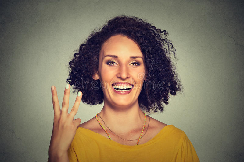 Young pretty woman giving a three fingers sign gesture with hand. Closeup portrait of young pretty woman giving a three fingers sign gesture with hand isolated stock photography