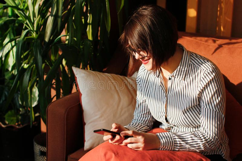 Young pretty woman with glasses looks into her smartphone and smiles. Young beautiful brunette on the orange sofa in the royalty free stock images