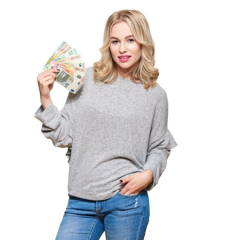 Young pretty woman in grey sweater holding bunch of Euro banknotes, looking at camera and smiling, isolated on white background. royalty free stock photography