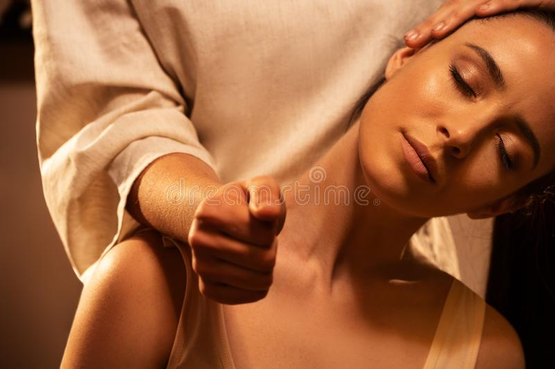 Young pretty woman has Thai massage. Close up of neck stretching. Concept of serene spa treatments. royalty free stock photography