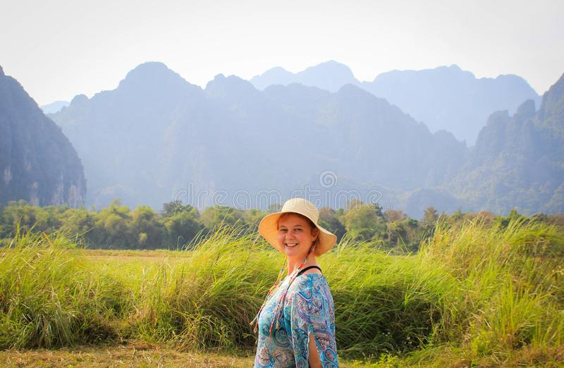 Young pretty woman in hat and blue dress is smiling at sunrise against the background of beautiful karst mountains in the village. Of Vang Vieng, Laos stock images