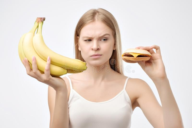 Choice eat food concept background. Young pretty woman holding banana and burger. Make a desicion about healthy diet stock photos