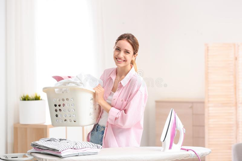 Young pretty woman holding basket of clean laundry at ironing board. Indoors royalty free stock image