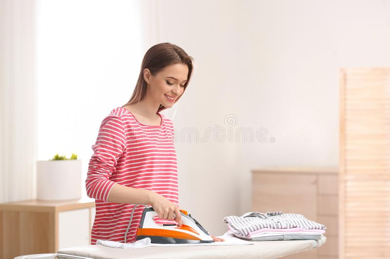 Young pretty woman ironing clean laundry indoors. Space for text stock image