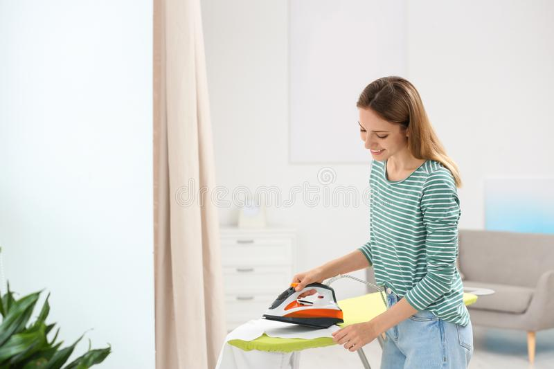 Young pretty woman ironing clean laundry indoors. Space for text royalty free stock photography