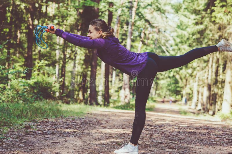 Young woman jogging and making exercises in the sunny forest royalty free stock photos