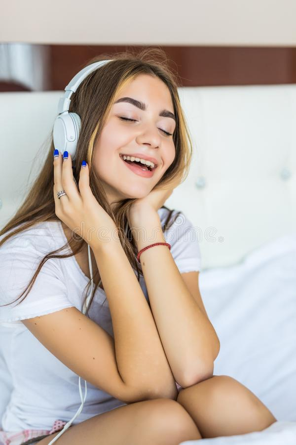Young pretty woman listening to music in headphones on bed. Young woman listening to music in headphones on bed stock images