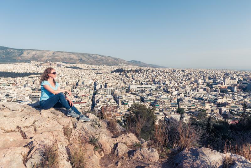 Young pretty woman looks at Athens city, Greece. Beautiful adult girl tourist relaxes overlooking Athens in summer royalty free stock image