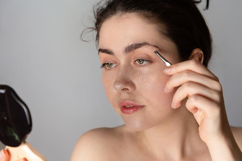 Young pretty woman looks in a compact mirror and corrects the shape of the eyebrows. The concept of getting rid of unwanted hair stock photography