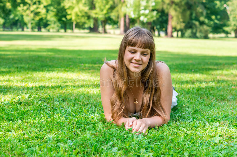 Young pretty woman lying on the grass stock photos
