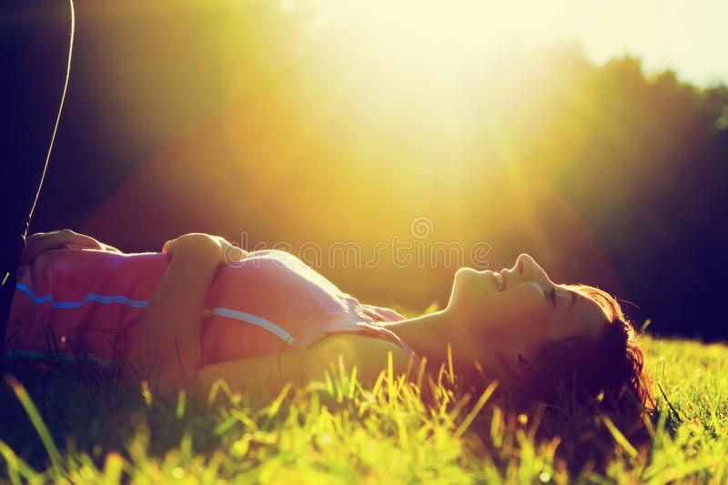 Young pretty woman lying on the grass at summer sunset stock photos