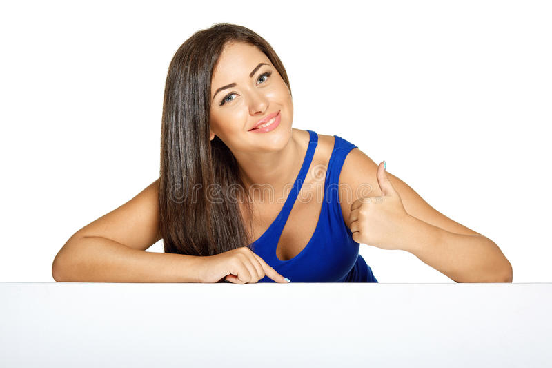 Young pretty woman peeking out from behind the stock image