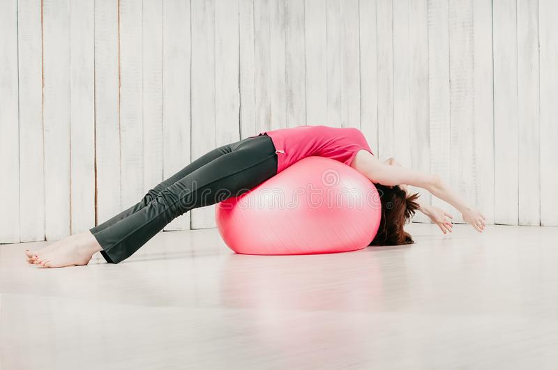 A girl holding balance lying pose over a pink fitball in a gym royalty free stock images