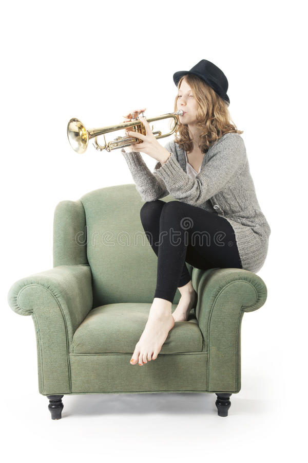 Young pretty woman playing the trumpet sitting on armchair royalty free stock photography