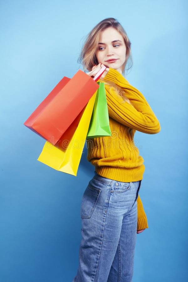 Young pretty woman posing emotional on blue background with bags, lifestyle people concept. Closeup royalty free stock photography