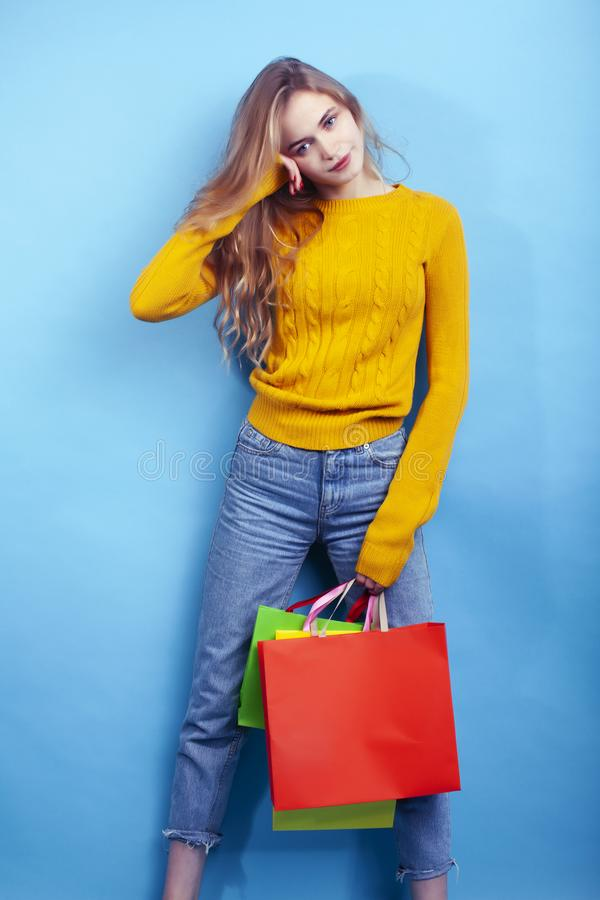 Young pretty woman posing emotional on blue background with bags, lifestyle people concept. Closeup stock images