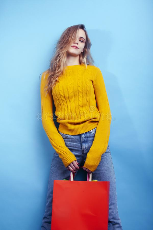 Young pretty woman posing emotional on blue background with bags, lifestyle people concept. Closeup stock image