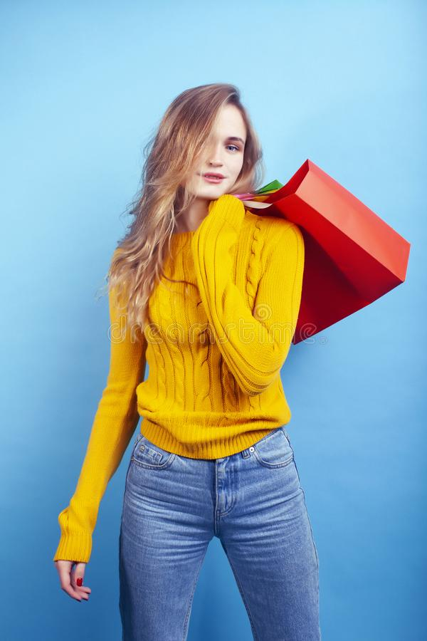 Young pretty woman posing emotional on blue background with bags, lifestyle people concept. Closeup royalty free stock image